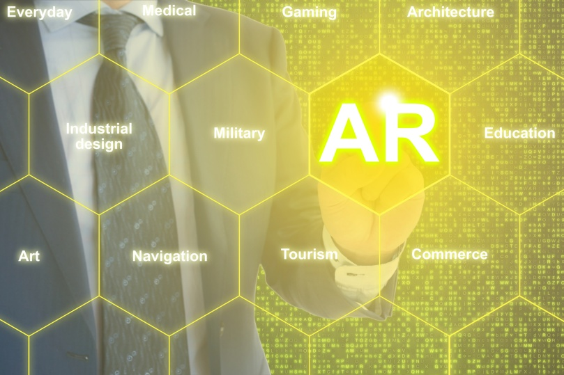 IT expert touching a hexagon grid with the letters AR for augmented reality and surrounding fields of usage